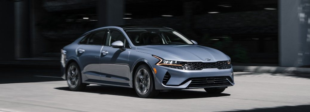 2021 Kia K5 driving on road from exterior front