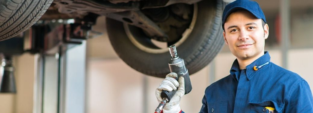 Mechanic holding drill with car tires in background