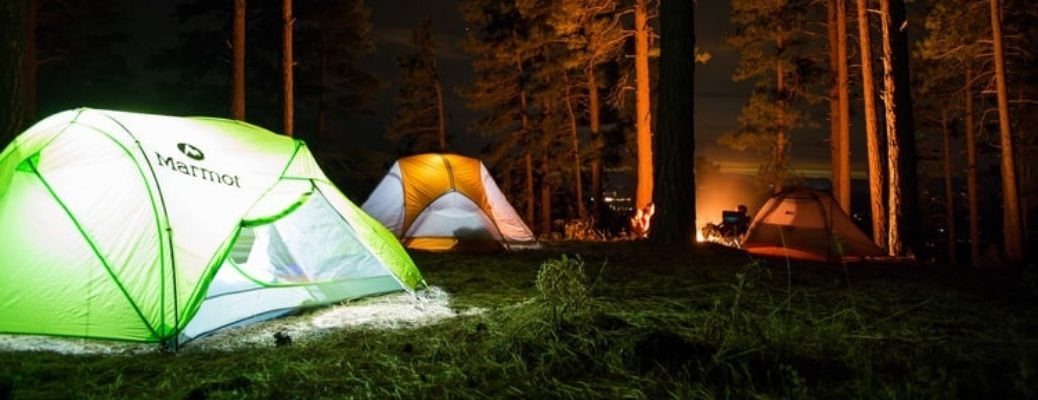 A close-up of three camp tents in the middle of the forest
