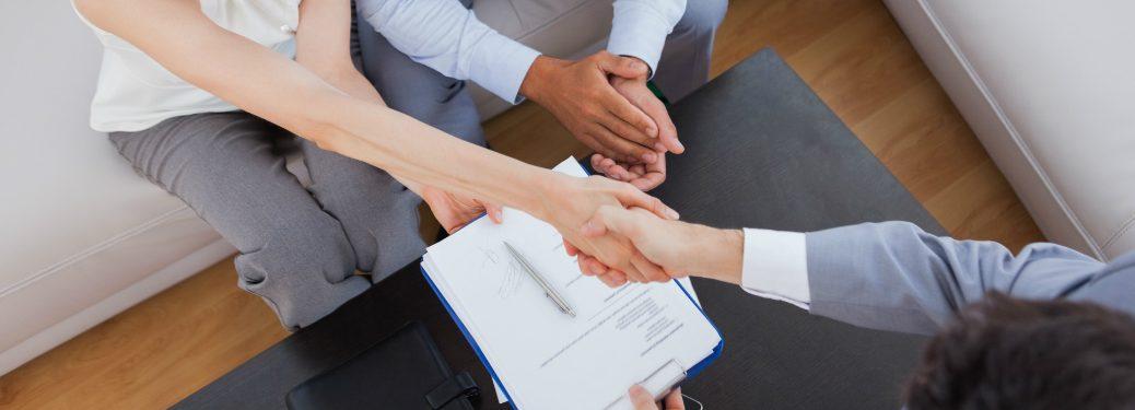 driver and dealership sales person shaking hands with paperwork