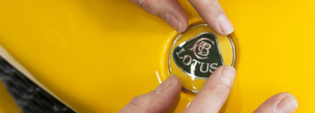 hands putting lotus badge on a yellow car