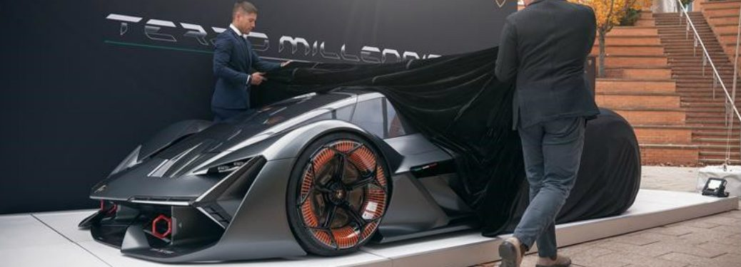 two people taking a sheet of the lamborghini terzo millenio ev concept