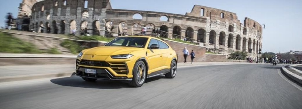Yellow 2019 Lamborghini Urus on City Street with Roman Coliseum in Background