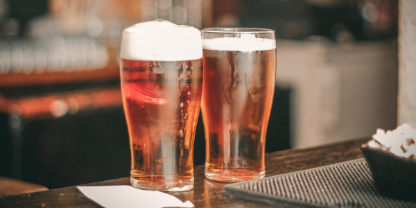 Two Beer Glasses on a Bar
