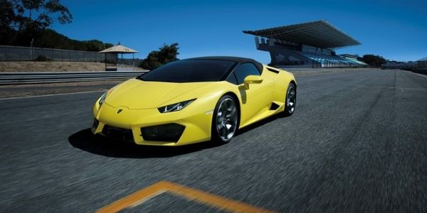 Yellow 2019 Lamborghini Huracan RWD Spyder on a Track with Black Convertible Top