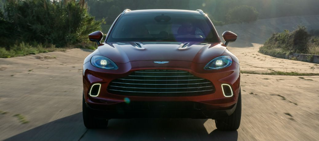 Head-on view of a red 2021 Aston Martin DBX driving up a dirt road.