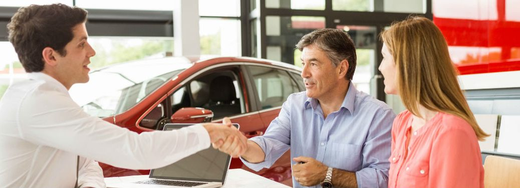 Customers shaking hands with salesman