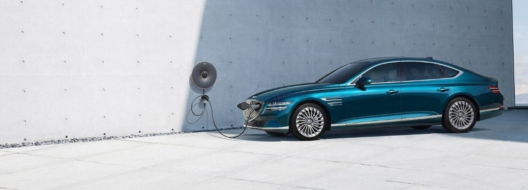 Blue 2022 Genesis Electrified G80 in a Driveway Charging