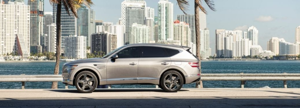 Silver 2021 Genesis GV80 Side Exterior Parked Next to Water and Palm Trees