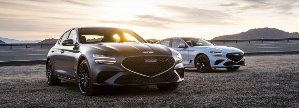 Gray and White 2022 Genesis G70 Models Next to a Highway at Sunrise