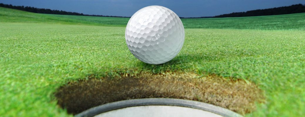 White golf ball coming to a stop at the edge of hole