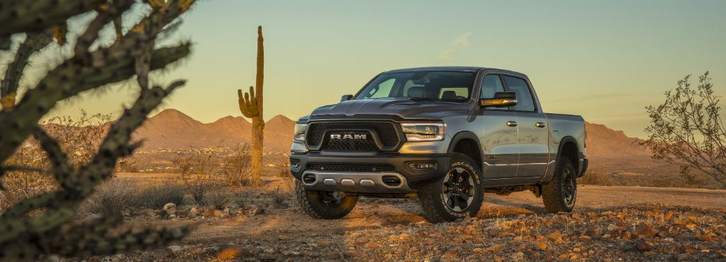 Driver side exterior view of a gray 2019 Ram 1500 driving through the desert