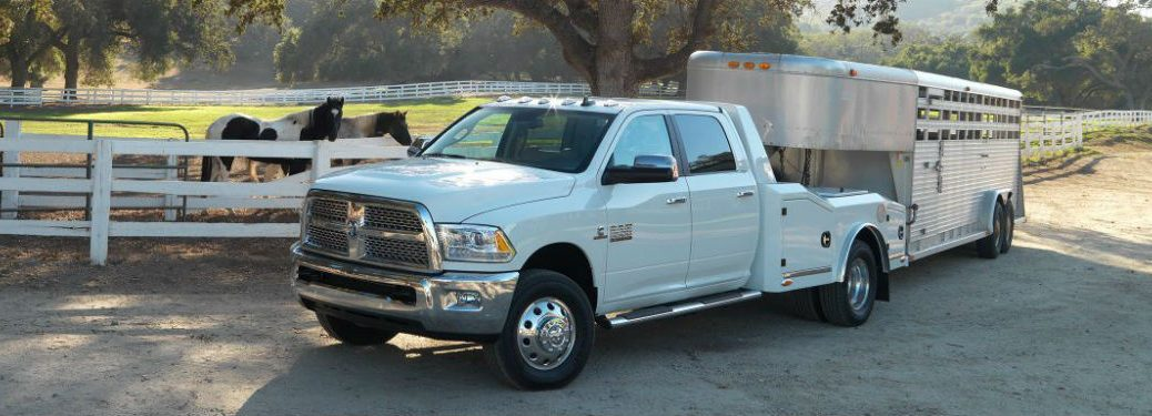 Driver side exterior view of a white 2018 Ram 2500 Chassis Cab towing a horse trailer