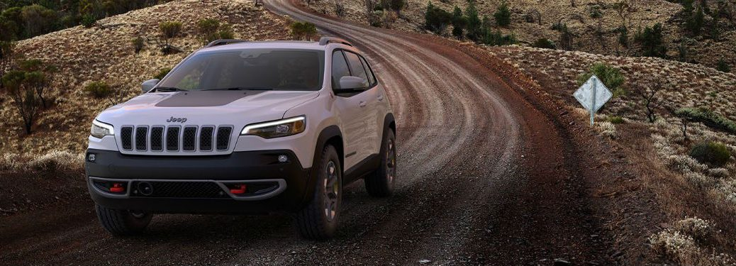 Front exterior view of a 2019 Jeep Cherokee driving down a dirt trail