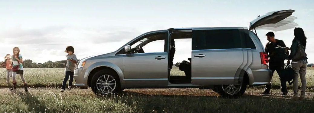 Driver side exterior view of a 2019 Dodge Grand Caravan with its rear tailgate open and side doors opening