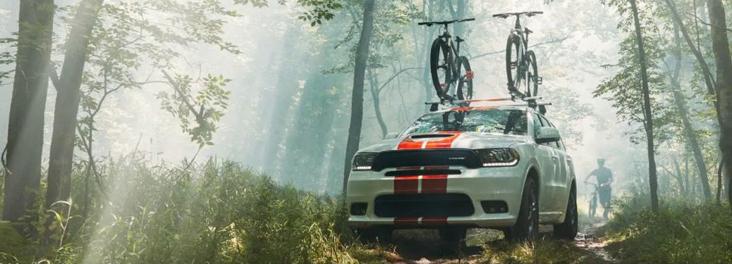 Front exterior view of a white 2019 Dodge Durango with orange racing stripes driving through the woods with bikes standing in a rack on its roof