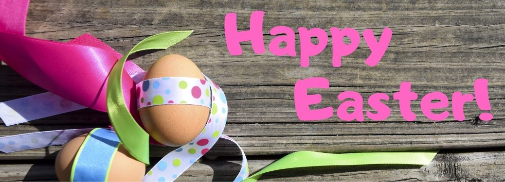 Easter Eggs with Ribbon on a Wood Background with Pink Happy Easter! Text