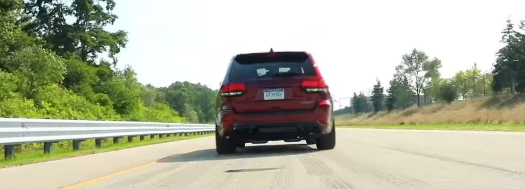 Rear view of red 2019 Jeep Grand Cherokee Trackhawk driving on a racetrack