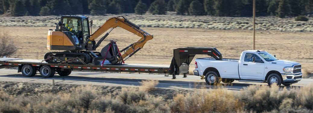 White 2019 Ram Heavy Duty towing a construction excavator