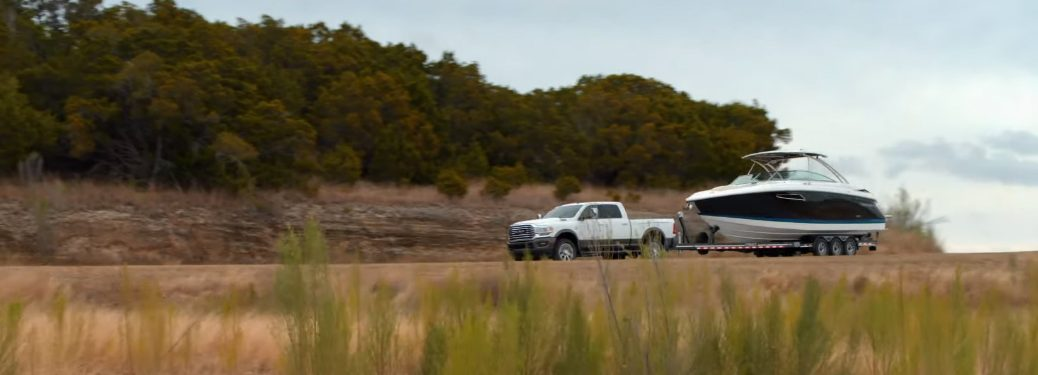 A white Ram truck towing a boat