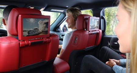 View of the dual-screen Blu-ray entertainment system with kids watching it and men sitting in front seats
