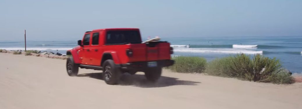 2020 Red Jeep Gladiator driving by the ocean at Huntington Beach