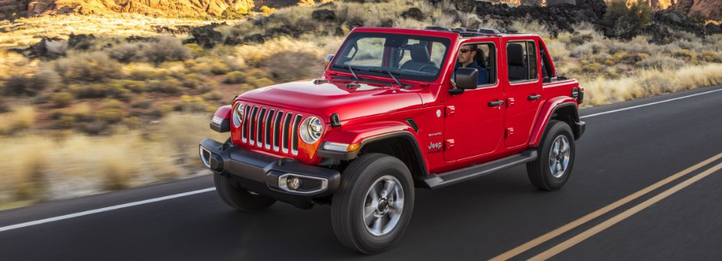 Red 2020 Jeep Wrangler driving by a desert landscape