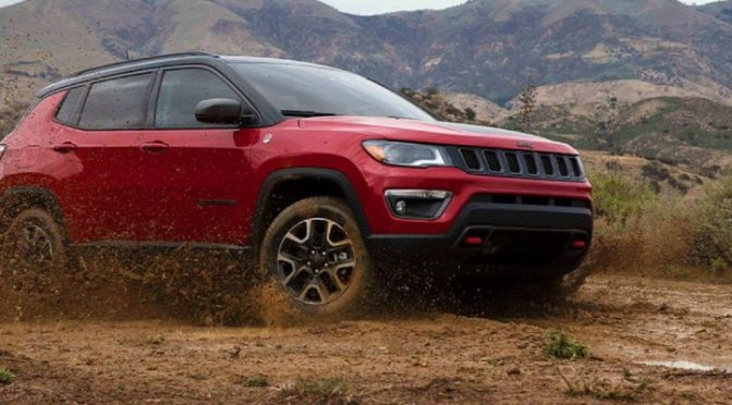 Red 2021 Jeep Compass parked on dirt path