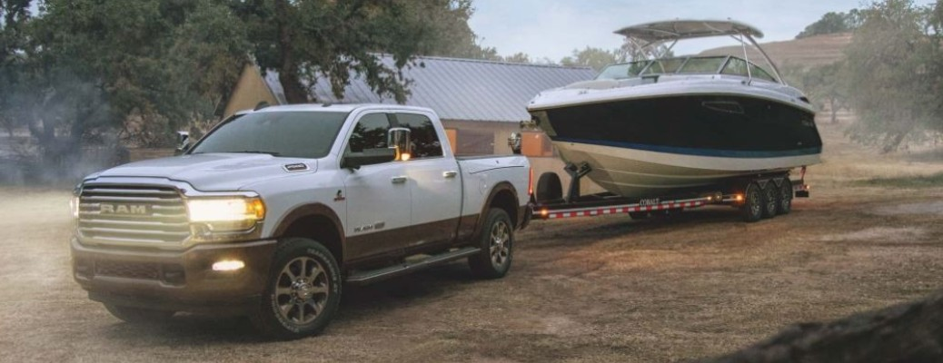 A white-colored 2021 RAM 2500 towing a boat down a road