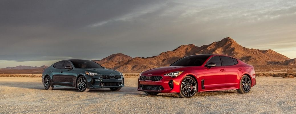 three-quarter view of two 2022 Kia Stinger GT and GT-Line parked in a desert
