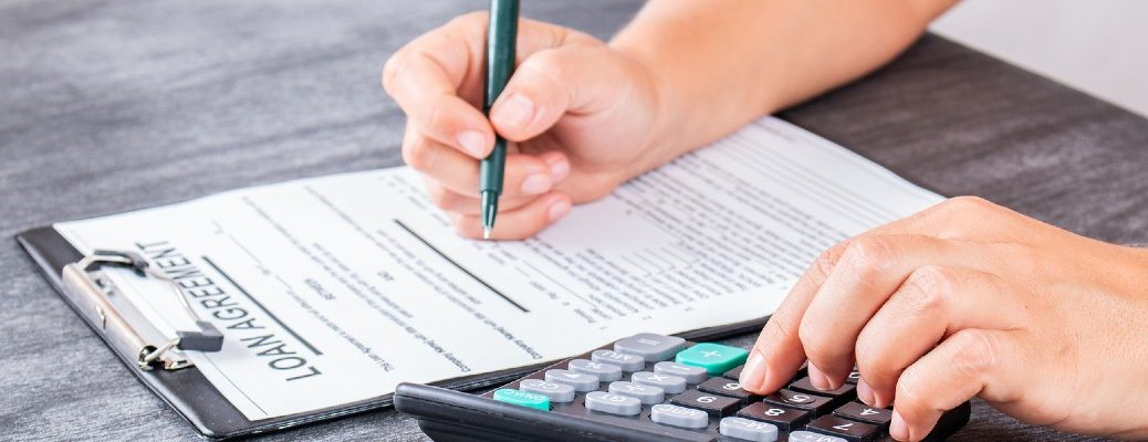 A stock photo of a person filling out a loan application.