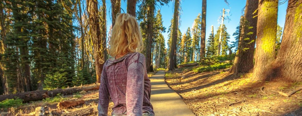 A stock photo of a person walking through the woods.