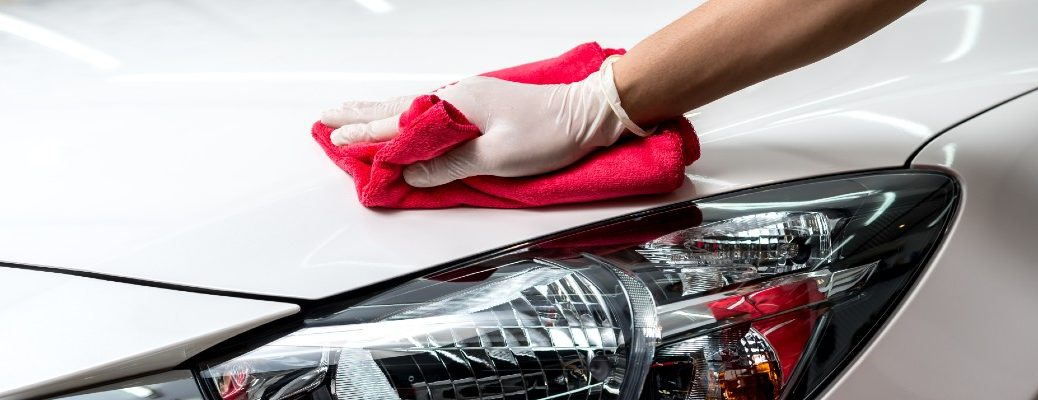 A stock photo of a person detailing a vehicle by hand.