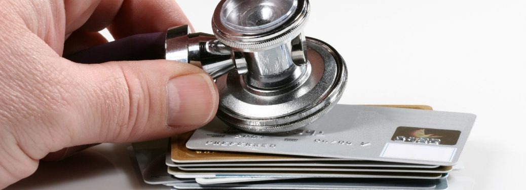 hand-holding-stethoscope-up-to-credit-cards