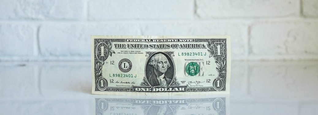 one-dollar-bill-on-white-table-with-white-brick-background