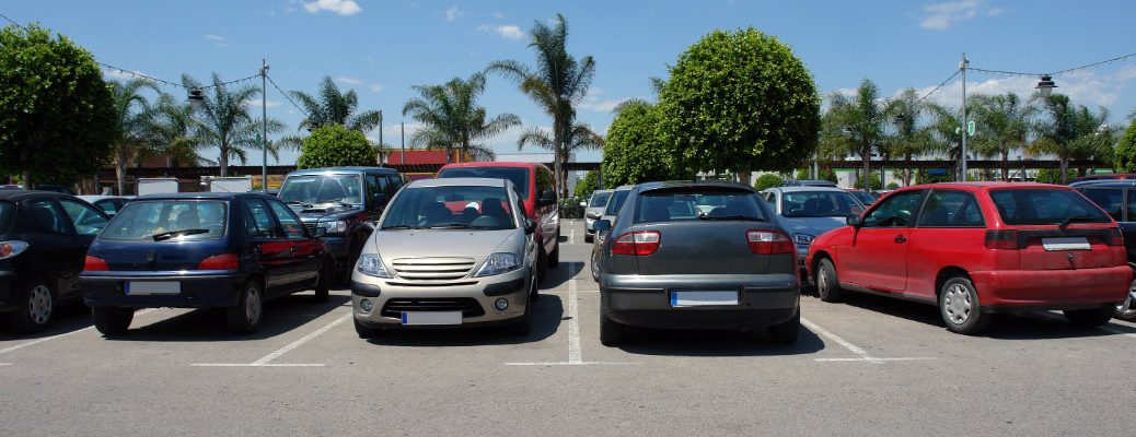 a line of cars parked in a lot for a pre-owned and used car dealership