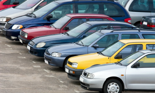 a line of car sedans with multiple colors parked on a lot