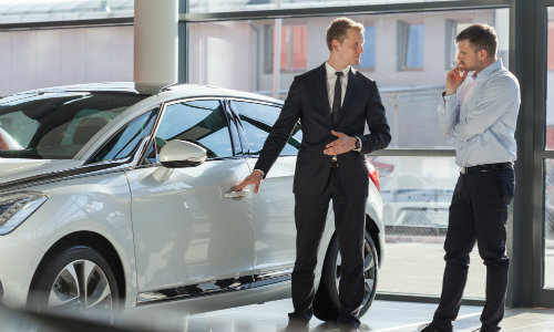 a car salesman at a dealership showing off a model to a wary customer