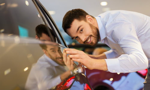 a car dealership salesman inspecting a vehicle on their floor