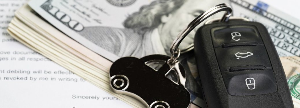 Car keys with money on top of a car loan application form