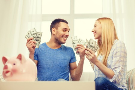 Happy couple holding money with a piggy bank sitting on a table in front