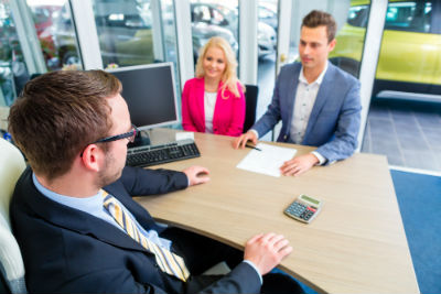 couple buying car at car dealership