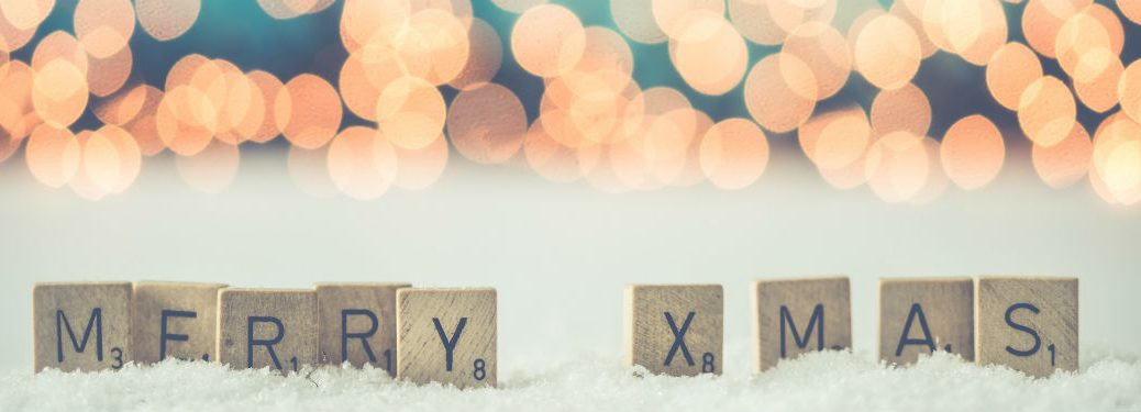 scrabble letters spelling merry xmas blurred lights background