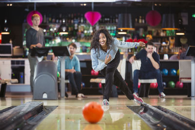 woman throwing bowling ball down three men behind her watching