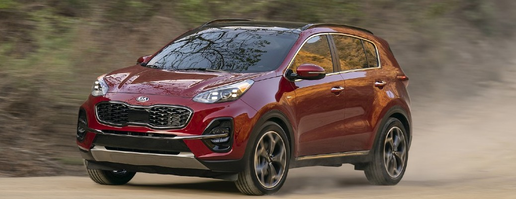 2021 Kia Sportage in red driving on dirt road