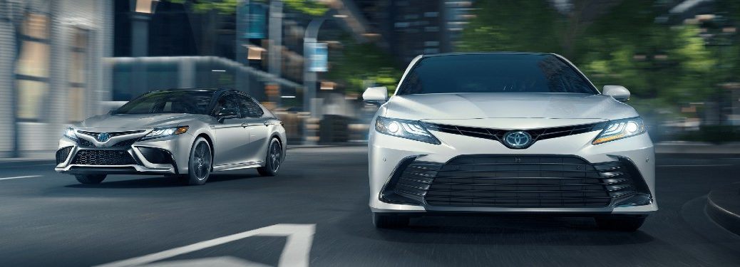 White 2021 Toyota Camry driving next to a silver 2021 Toyota Camry Hybrid