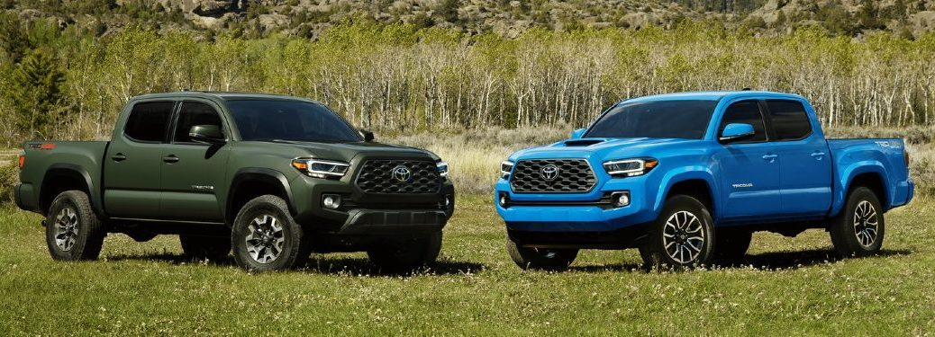 A green 2021 Toyota Tacoma and a blue 2021 Toyota Tacoma parked in a field