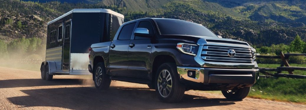 Front passenger angle of a black 2021 Toyota Tundra towing a trailer