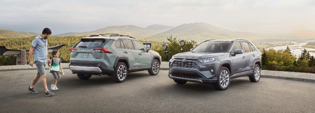 Father and son walking by two 2021 Toyota RAV4 vehicles