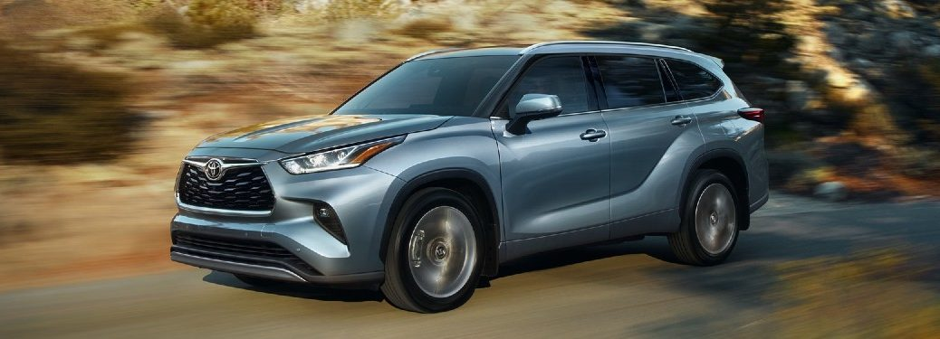 Front driver angle of a blue 2021 Toyota Highlander driving on a road